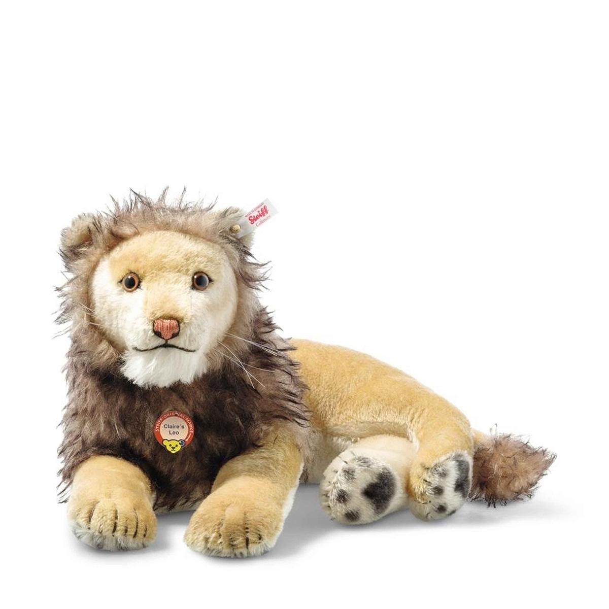 """Die """"Familienkollektion"""" von Steiff, die in limitierter Auflage erscheint, präsentiert Nachbildungen der beliebtesten Teddybären und Tiere, die Kinder dieser """"königlichen Familie"""" von Spielzeugmachern besessen haben. Zu jedem Sammlerstück aus Plüsch gehört ein schön gerahmtes Foto, auf dem das Kind und sein Spielzeug abgebildet sind. Nummer zwei in dieser Serie ist ein prächtiger und majestätischer Löwe, der einst Claire Steiff Meisel (der Enkelin von Richard Steiff) gehörte. Dieses königliche Geschöpf wurde mit größter Sorgfalt von Hand gefertigt, damit nichts vom Charme des Originals verloren geht. Jedes einzelne Stück ist ein eindrucksvolles Beispiel der Handwerkskunst von Steiff, die sich in aufwändigen Airbrush-Details, individuell gestickten Gesichtszügen und kunstvoll gemalten Pfoten zeigt. Dieses prachtvolle Exemplar wird in einer Auflage von nur 1.000 Stück herausgebracht. Mit seinem goldfarbenen """"Knopf im Ohr"""" verleiht Claires Dschungelkönig jeder Steiff Sammlung eine royale Note."""
